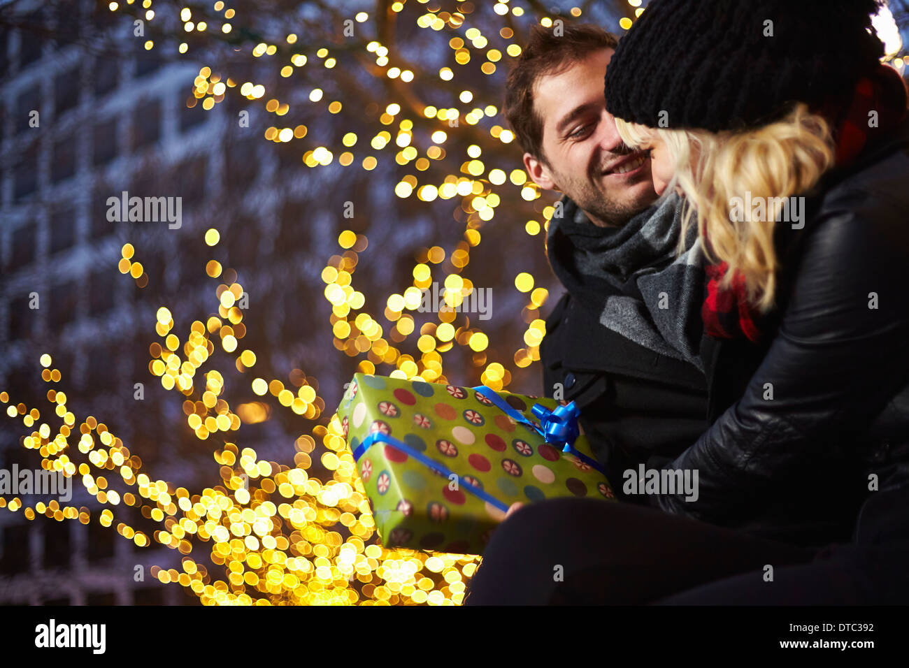 Young couple exchanging gifts next to outdoor xmas lights - Stock Image