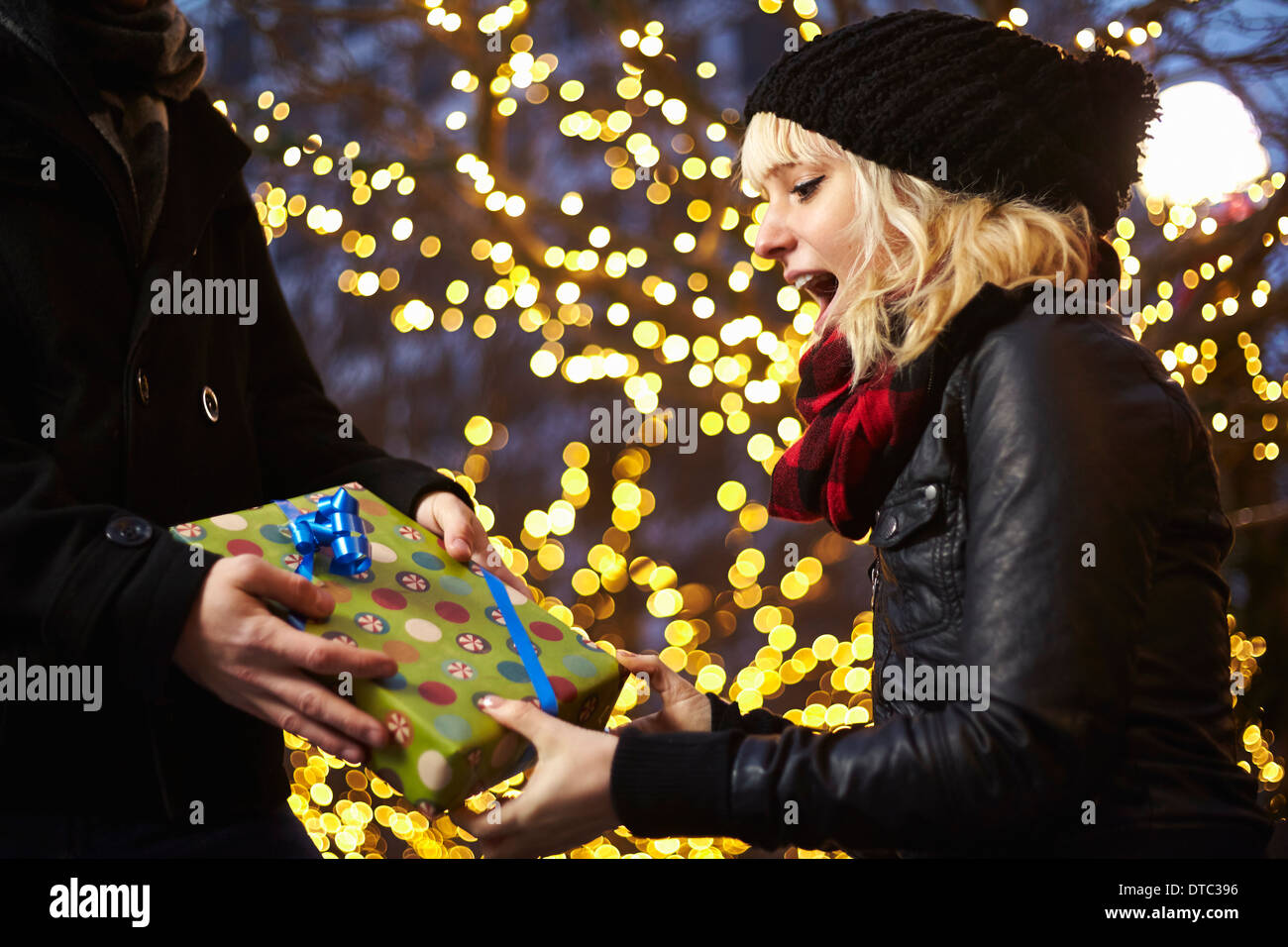 Young woman receiving xmas gift on city street - Stock Image