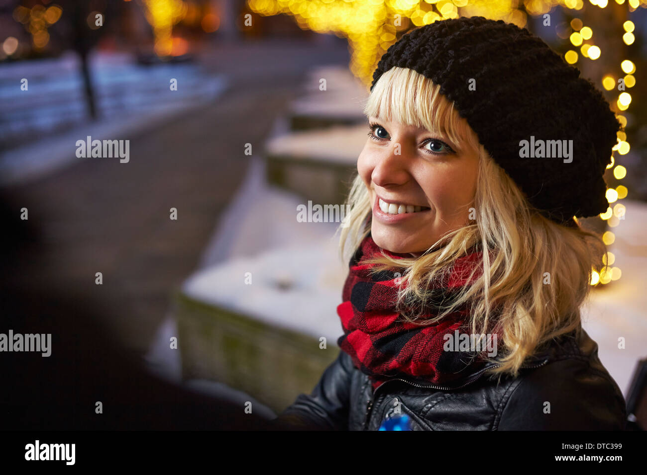 Young woman on city street with xmas lights - Stock Image