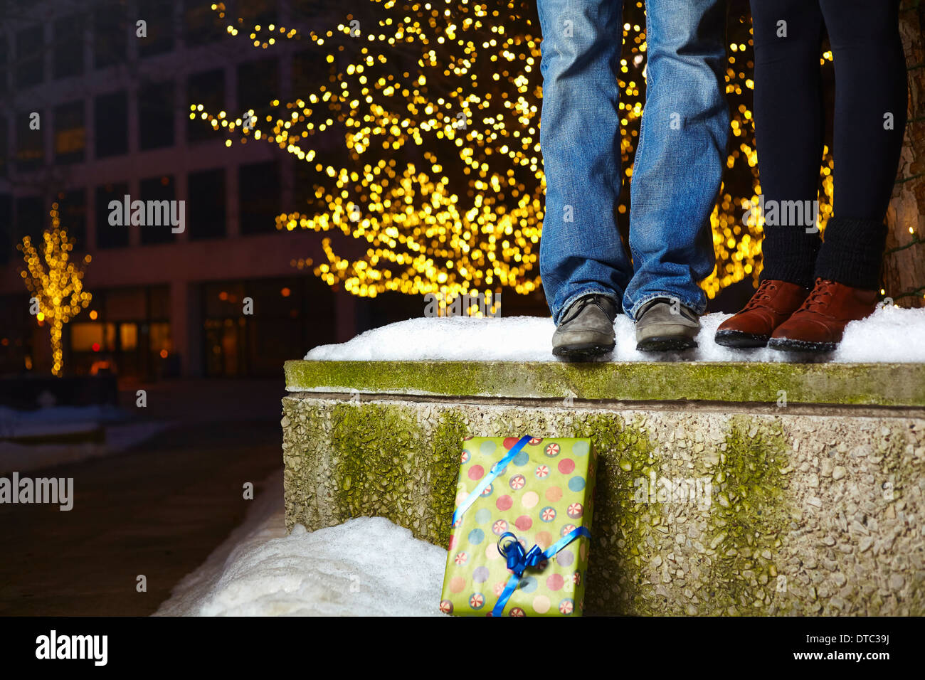 The legs of young couple standing on top of snow covered wall in city Stock Photo
