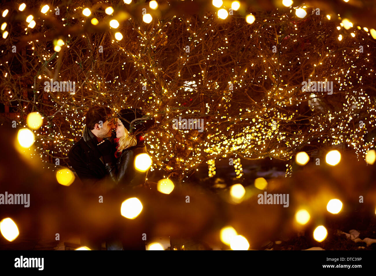 Young couple kissing surrounded by city xmas lights - Stock Image