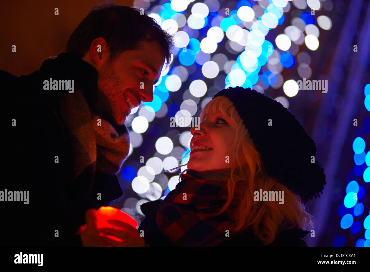 Young couple holding candle in front of city xmas lights - Stock Image