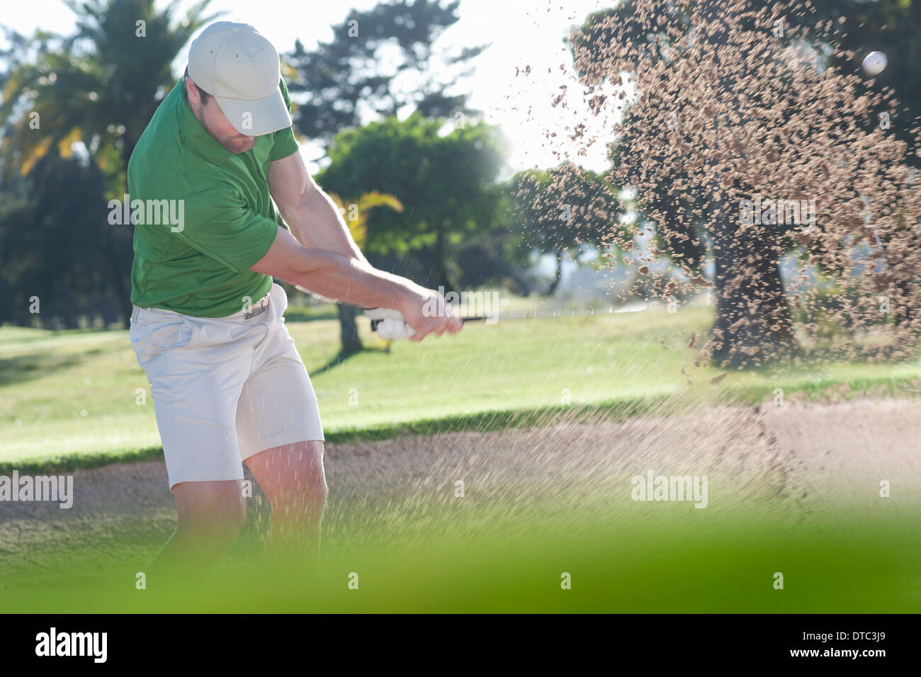 Young male golfer playing out of bunker - Stock Image
