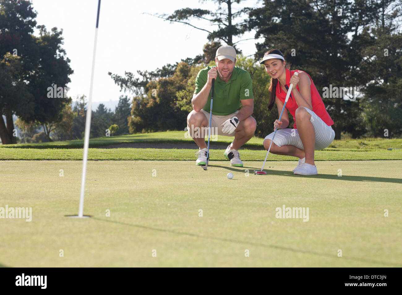 Young female golfer taking advice from trainer - Stock Image