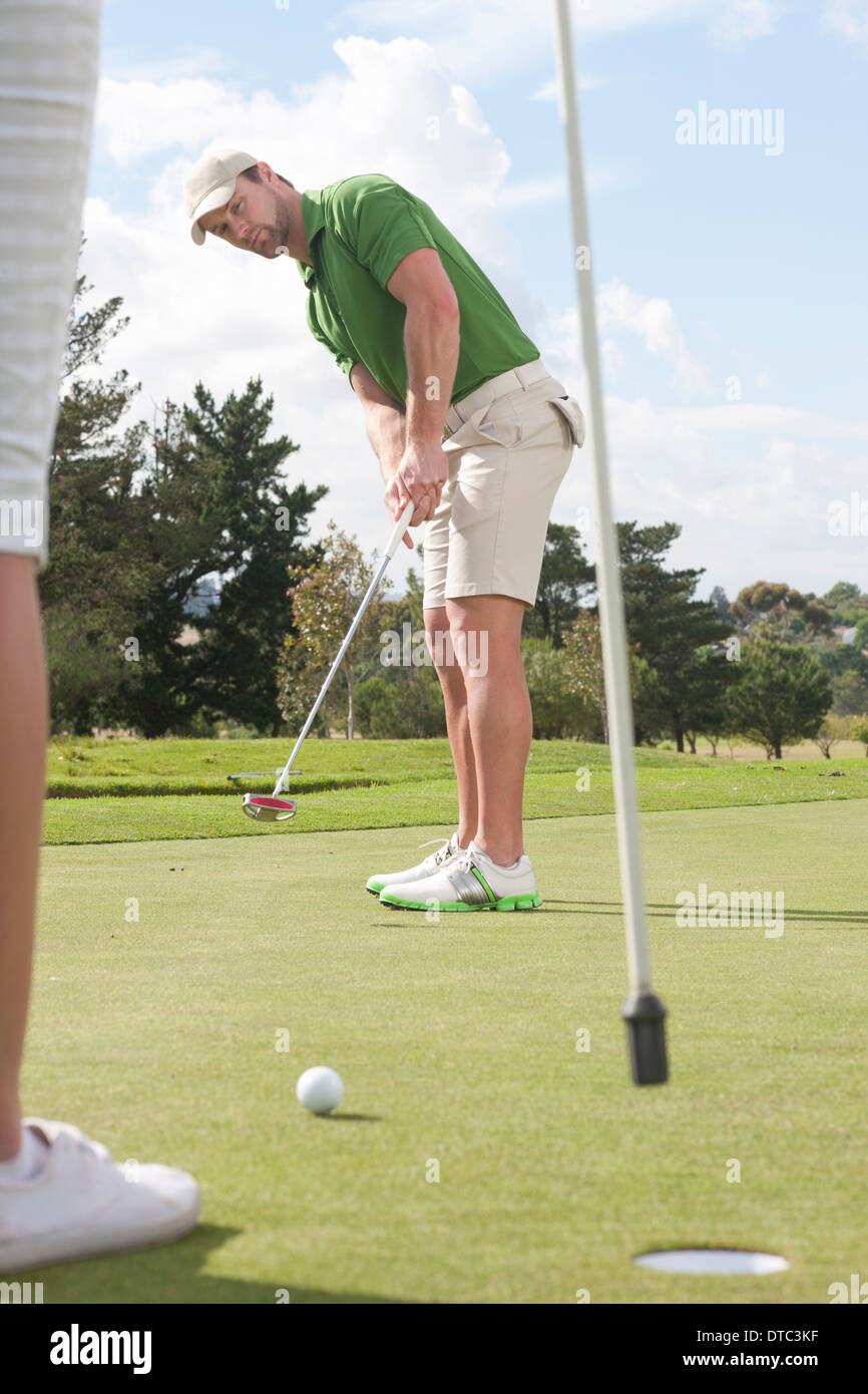 Young male golfer putting on golf green - Stock Image