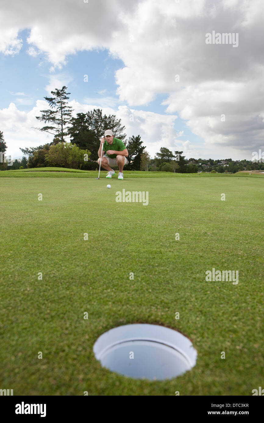 Young male golfer lining up the ball on the green - Stock Image
