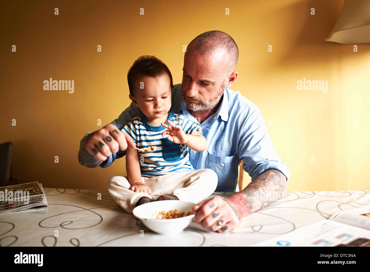 Baby boy sitting on table having cereal with father - Stock Image