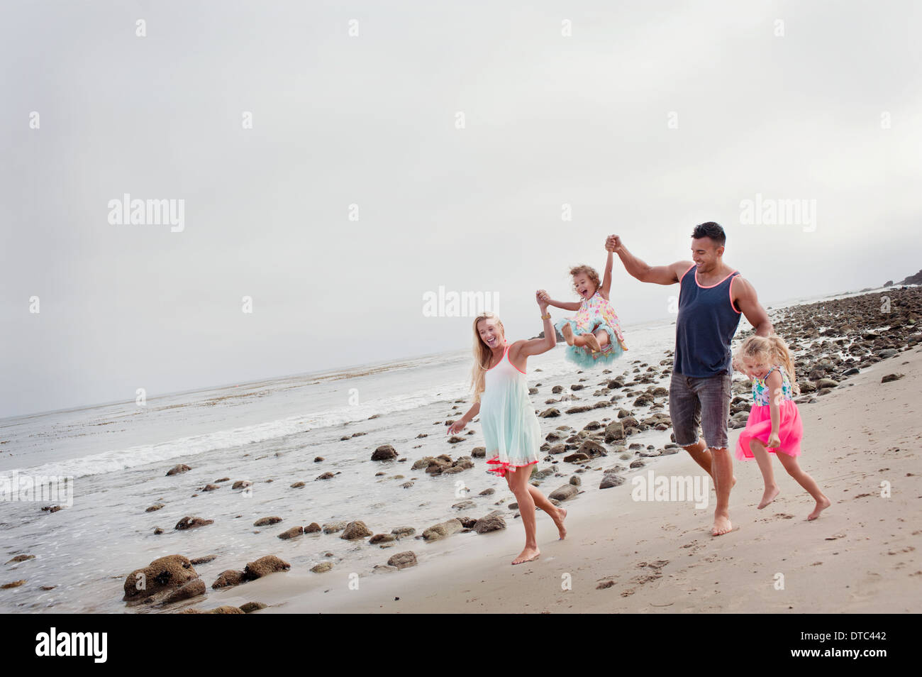 Parents and two young girls walking on beach - Stock Image