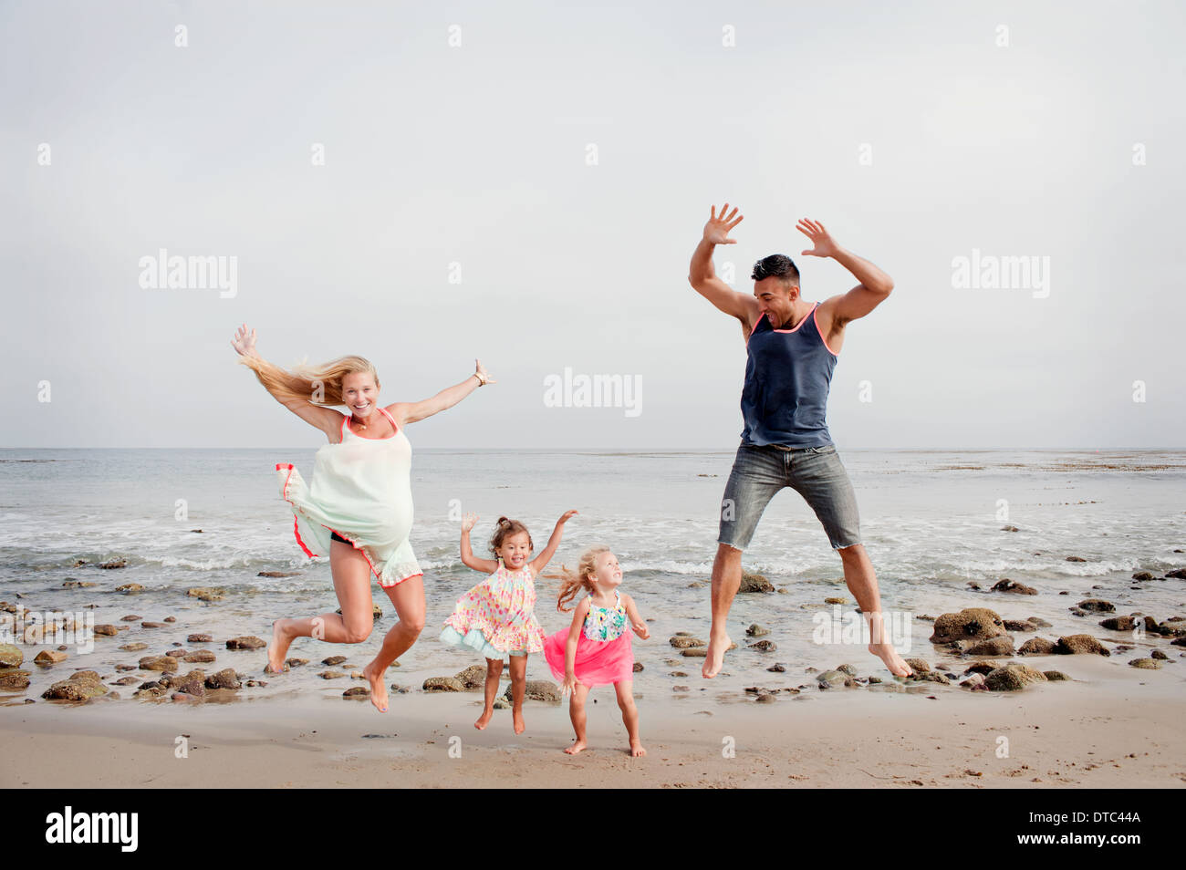 Parents and two young girls jumping mid air on beach - Stock Image