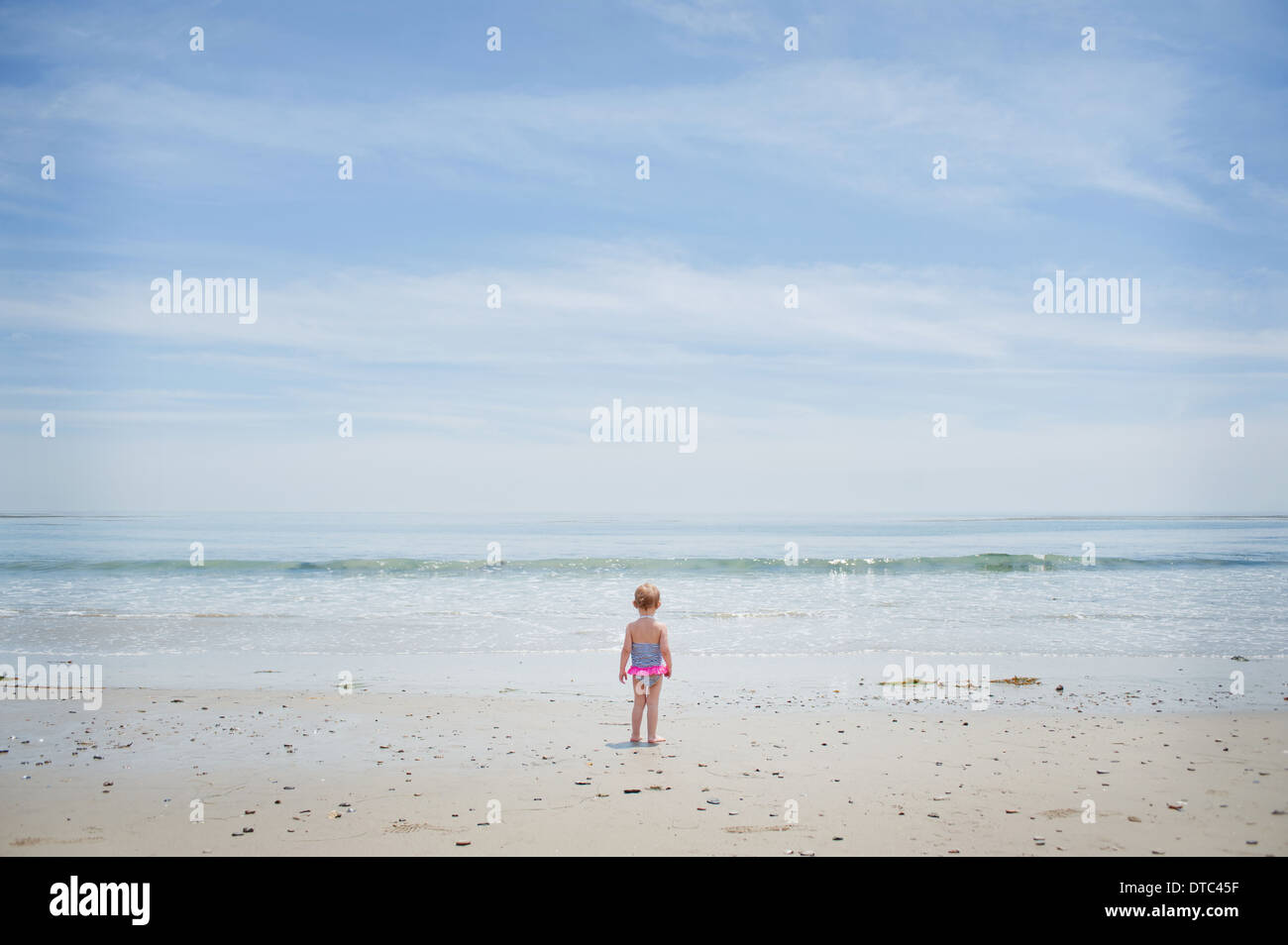 Apprehensive female toddler watching the sea - Stock Image