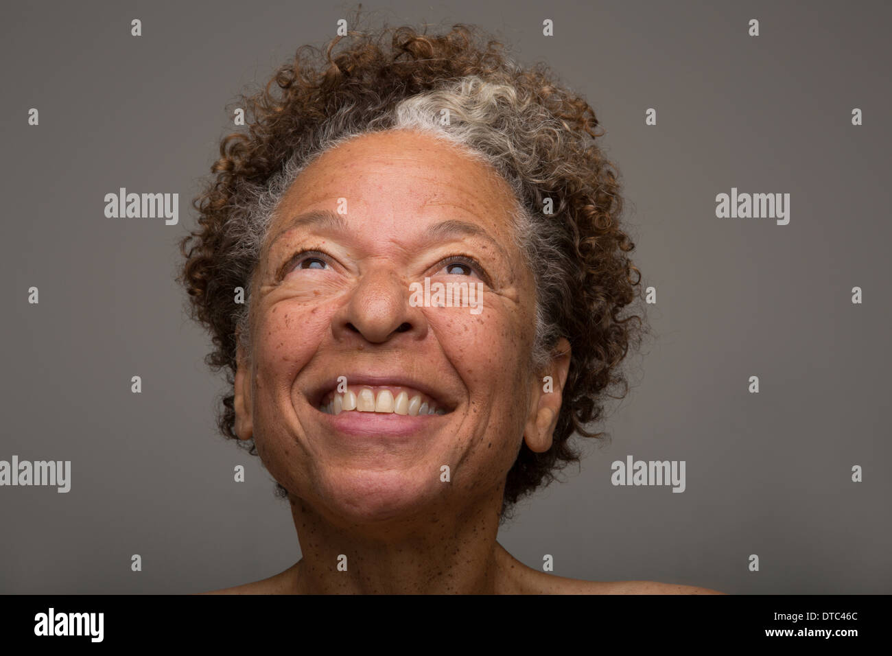 Close up studio portrait of smiling senior woman - Stock Image