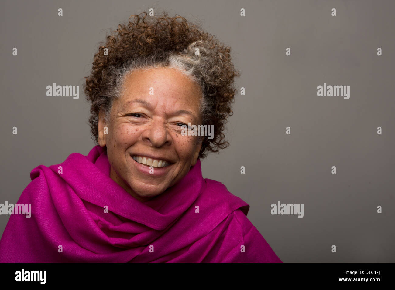 Studio portrait of happy senior woman in pink shawl Stock Photo