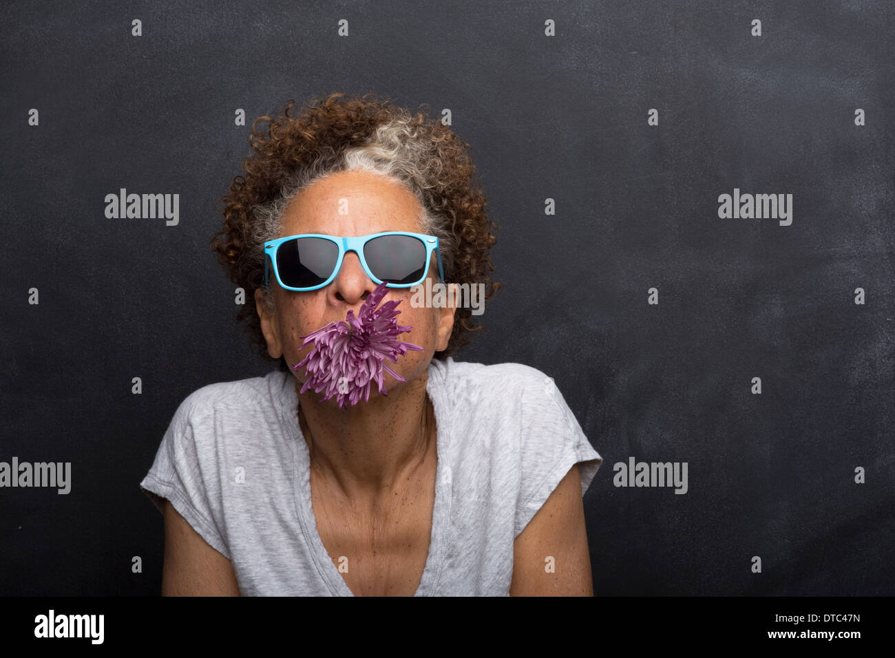 Studio portrait of senior woman with flower in her mouth - Stock Image