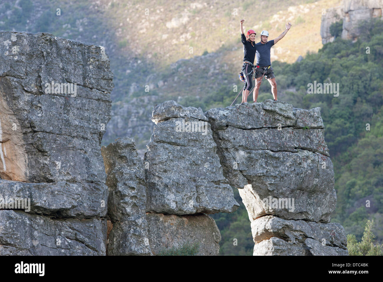 Young rock climbing couple celebrating on rock formation - Stock Image