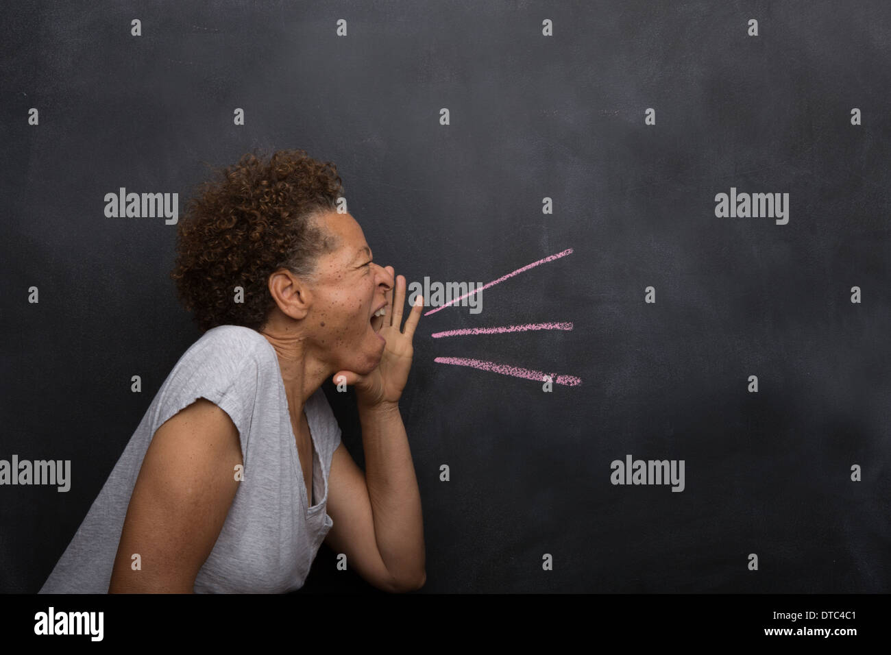 Senior woman in front of blackboard pretending to shout - Stock Image