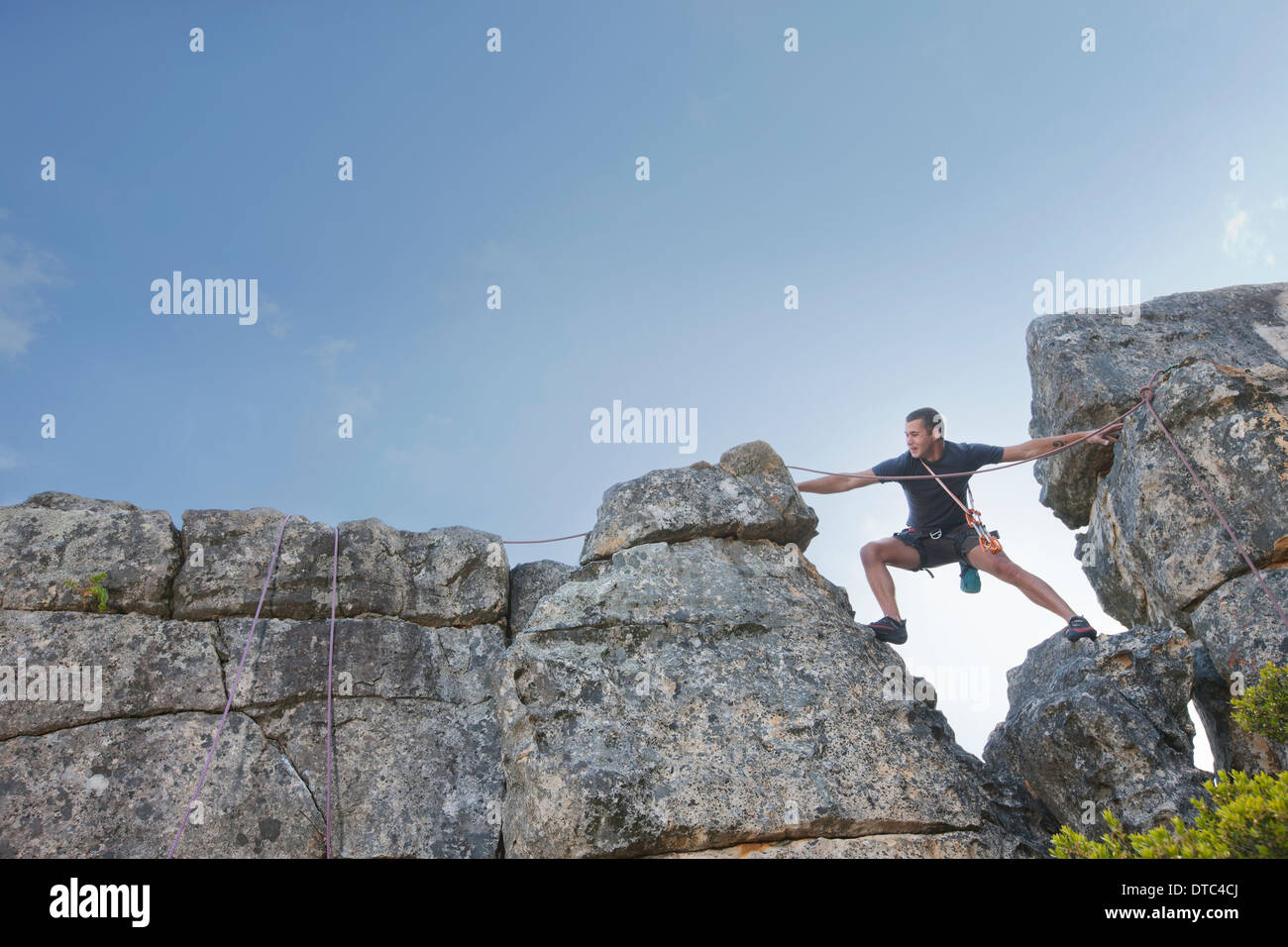 Young man stepping and reaching on rock climb - Stock Image