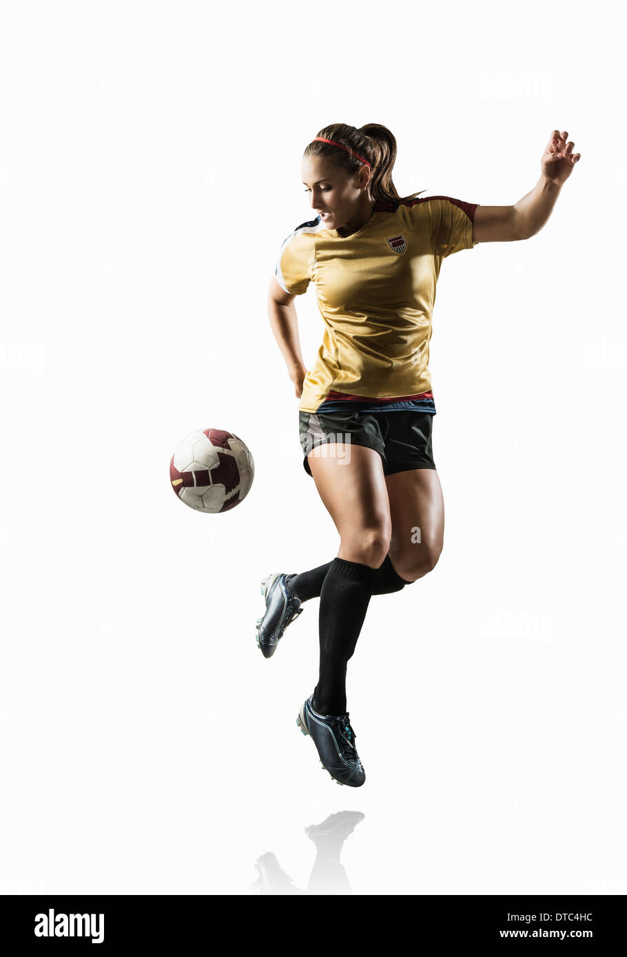Studio shot of young female soccer player back kicking ball - Stock Image