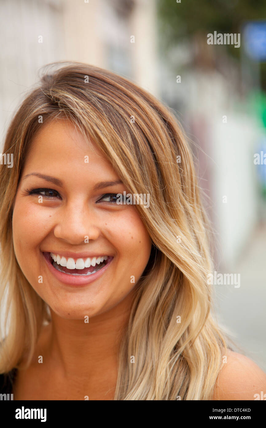 Portrait of young woman with blonde hair smiling - Stock Image