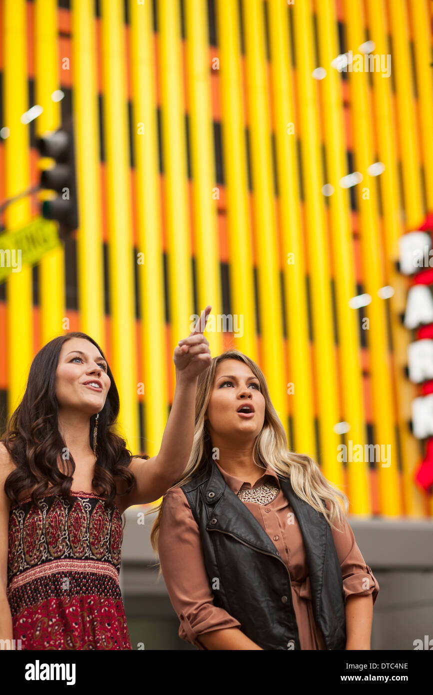 Young woman with friend in city pointing - Stock Image