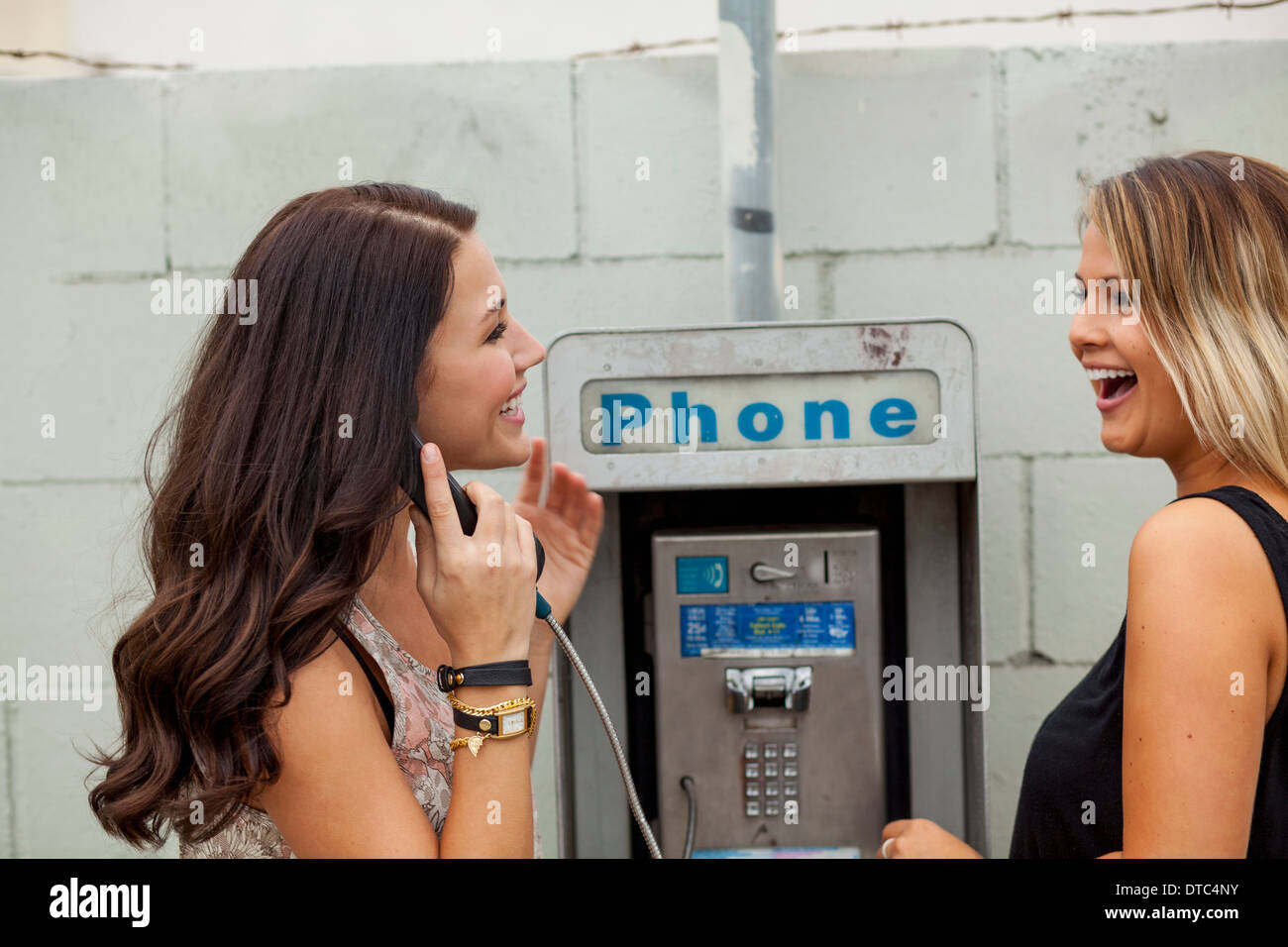 Young women using payphone laughing - Stock Image