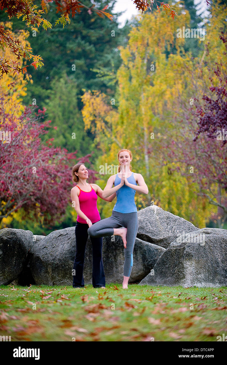 Yoga instructor teaching young woman in forest - Stock Image