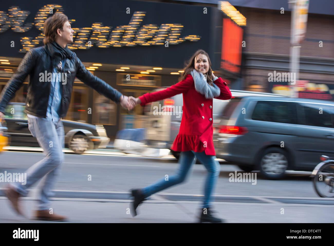 Young couple running along street, New York City, USA - Stock Image
