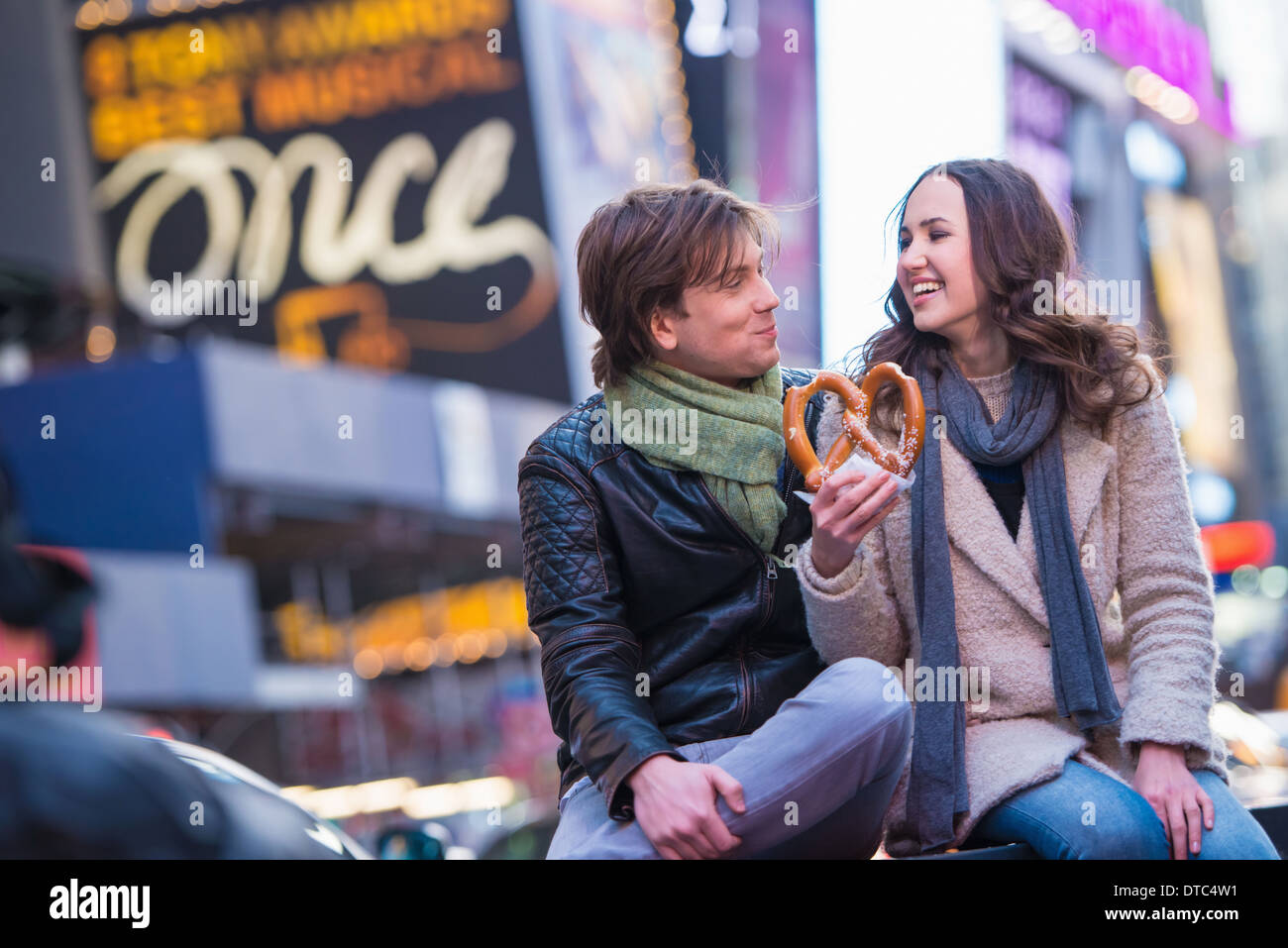 Young couple sharing pretzel, New York City, USA - Stock Image