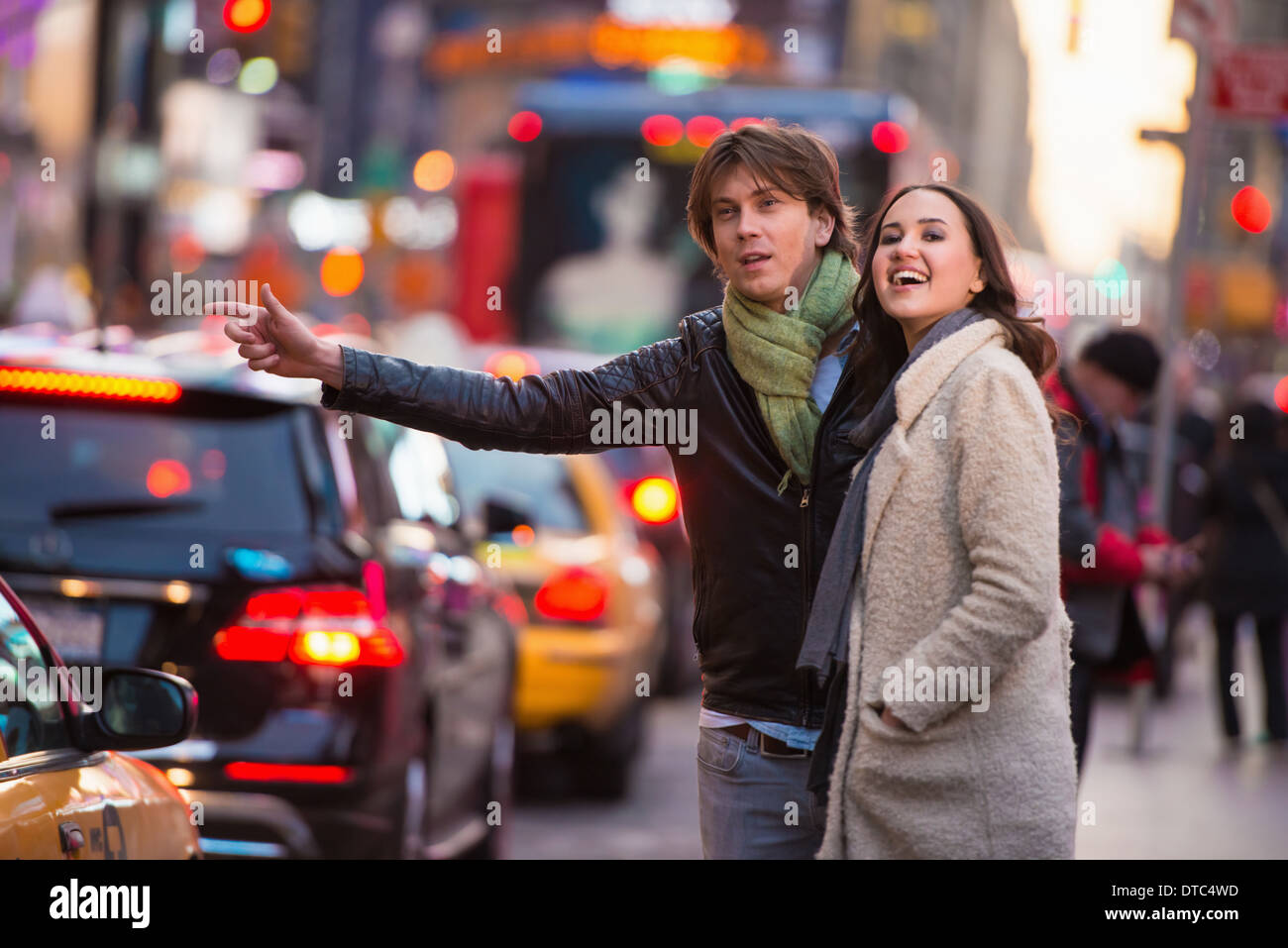 Young tourist couple hailing a cab, New York City, USA - Stock Image
