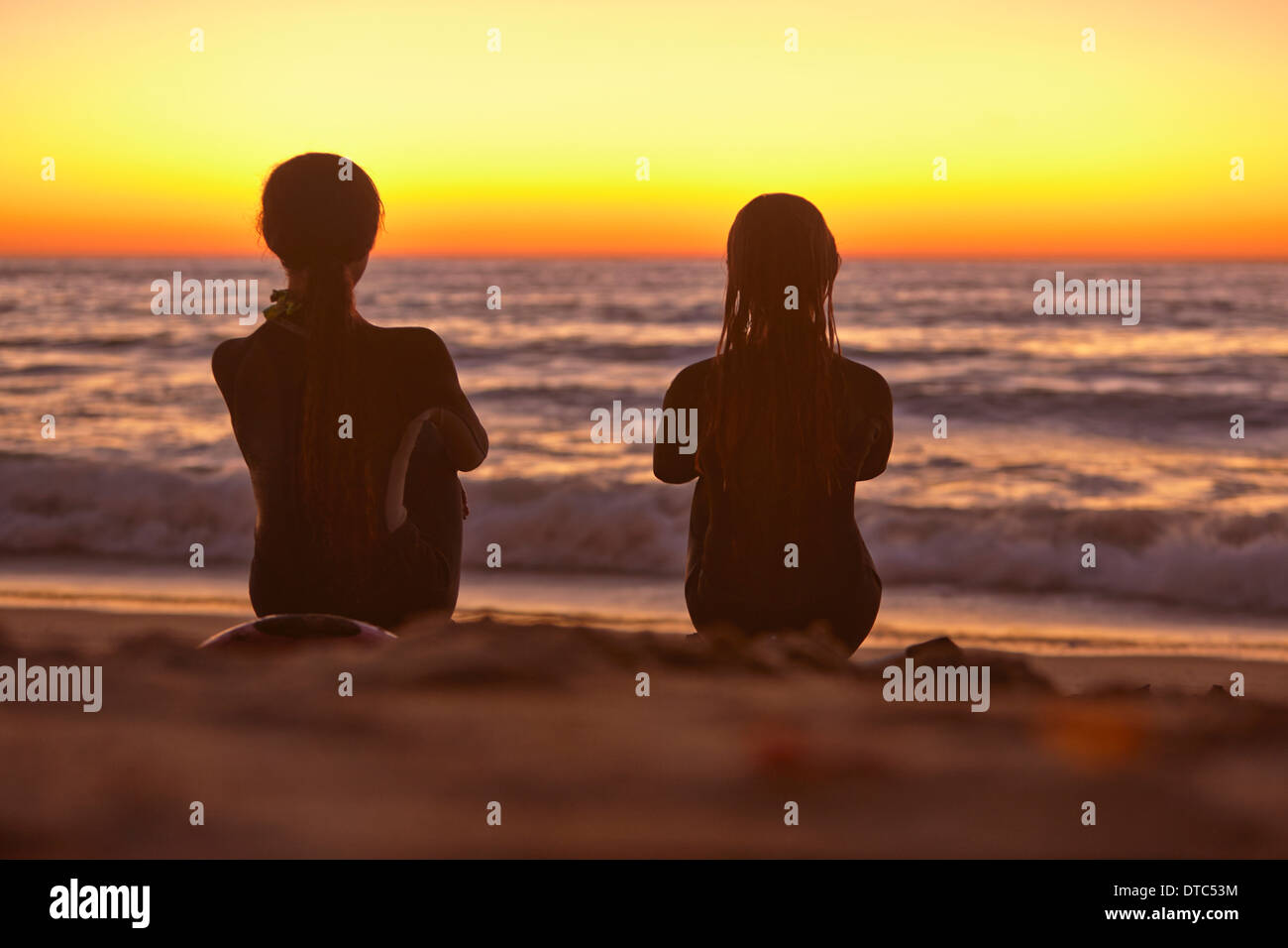 Two girls sitting on beach at sunset looking out to sea - Stock Image
