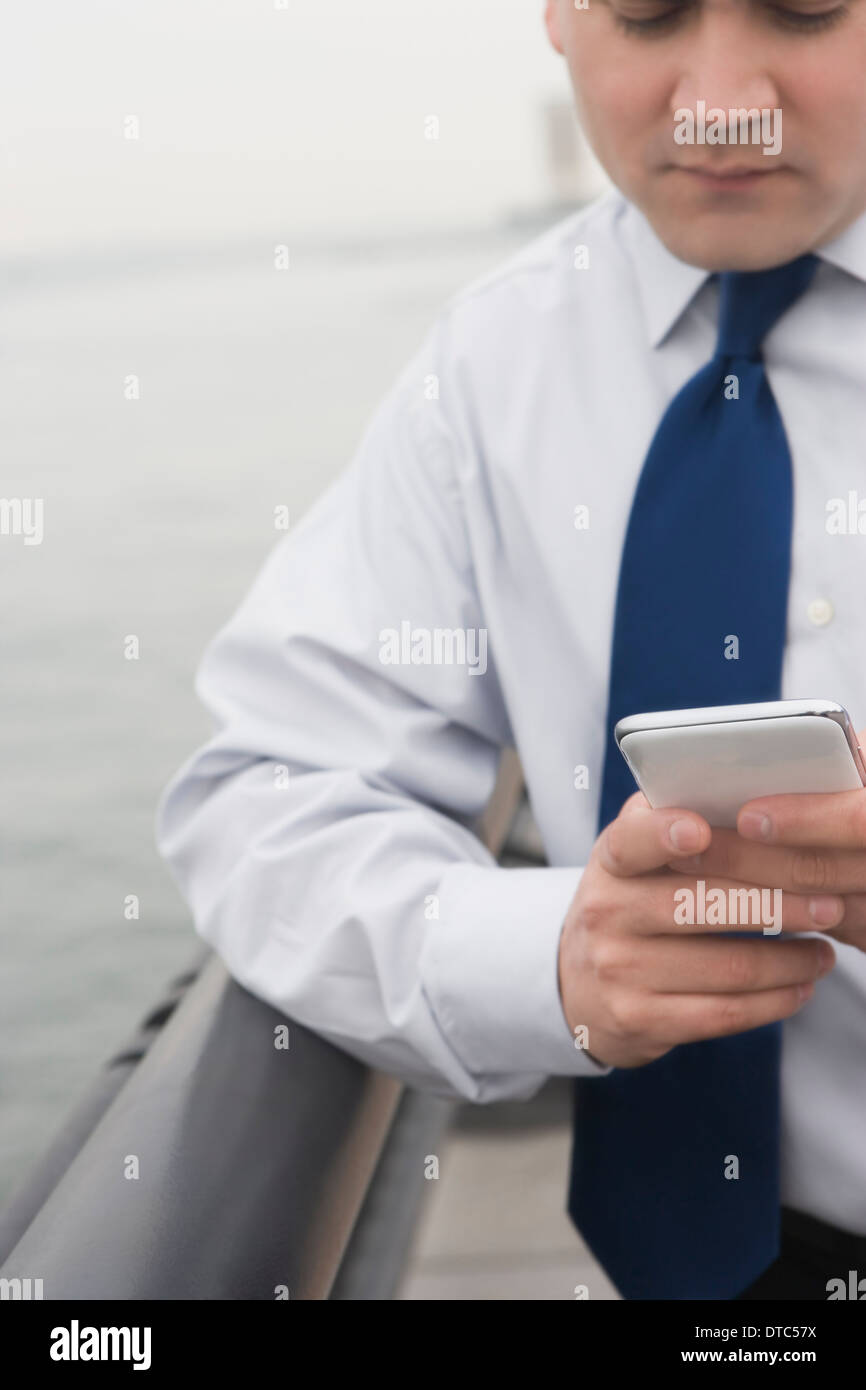 Businessman leaning on rail texting - Stock Image
