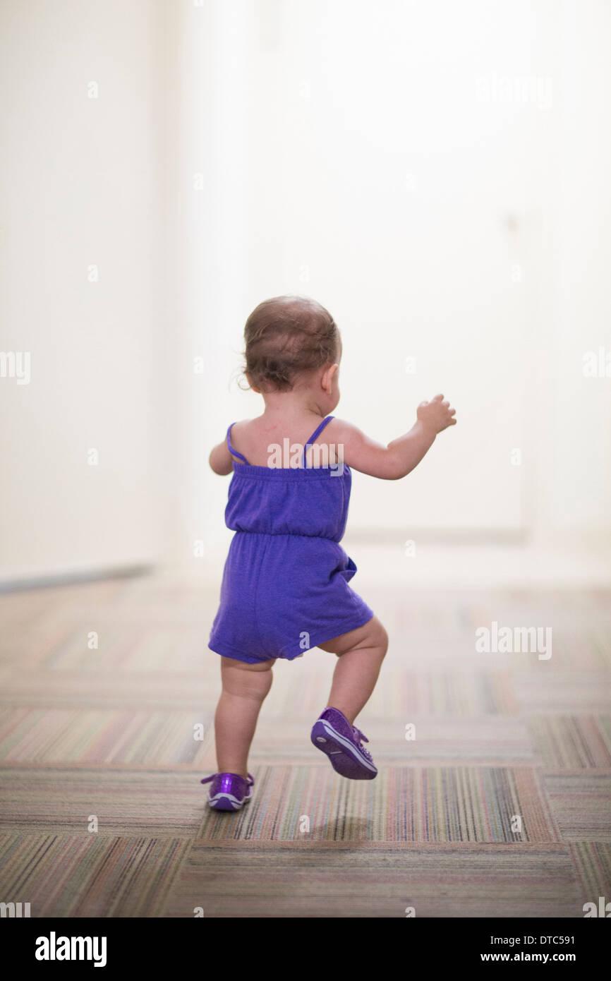 Toddler girl learning to walk - Stock Image
