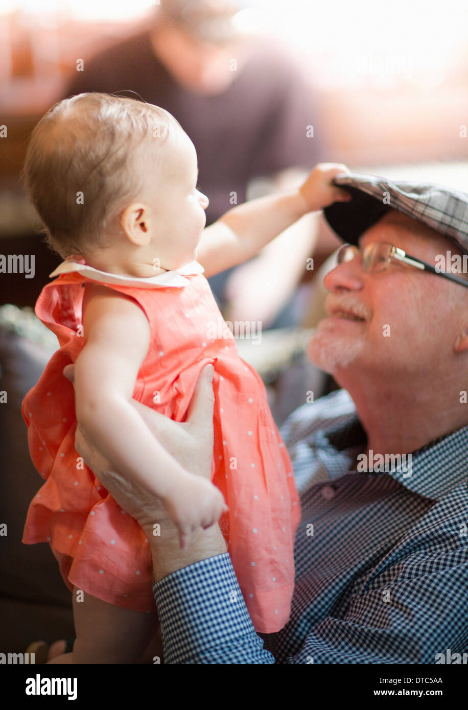 Grandfather holding granddaughter - Stock Image