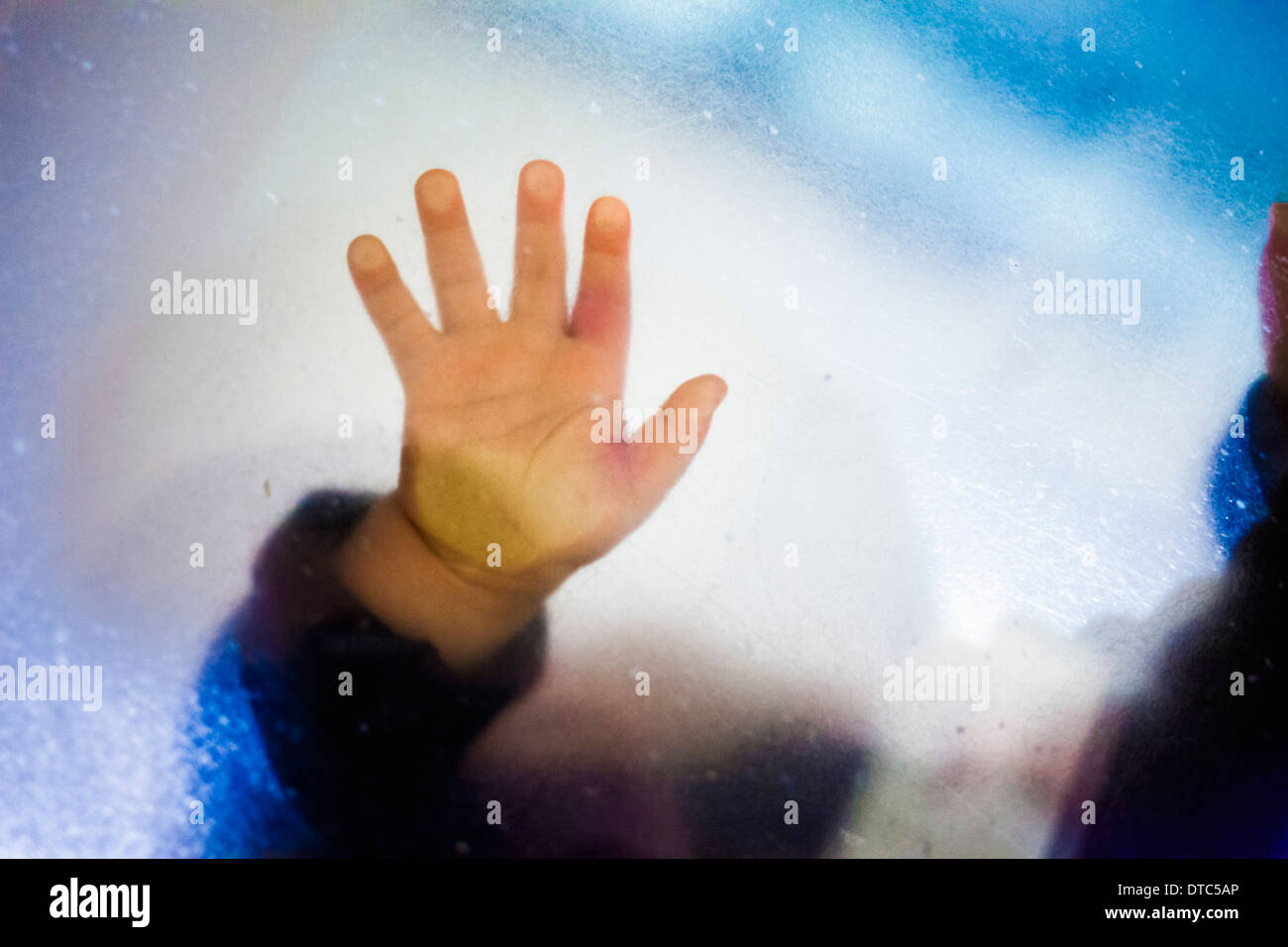 Toddler girl's hand touching glass - Stock Image