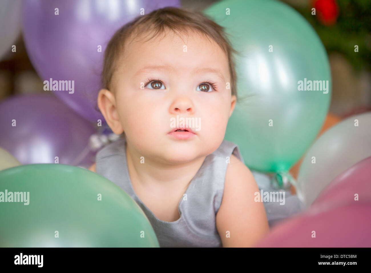 Baby girl with balloons - Stock Image