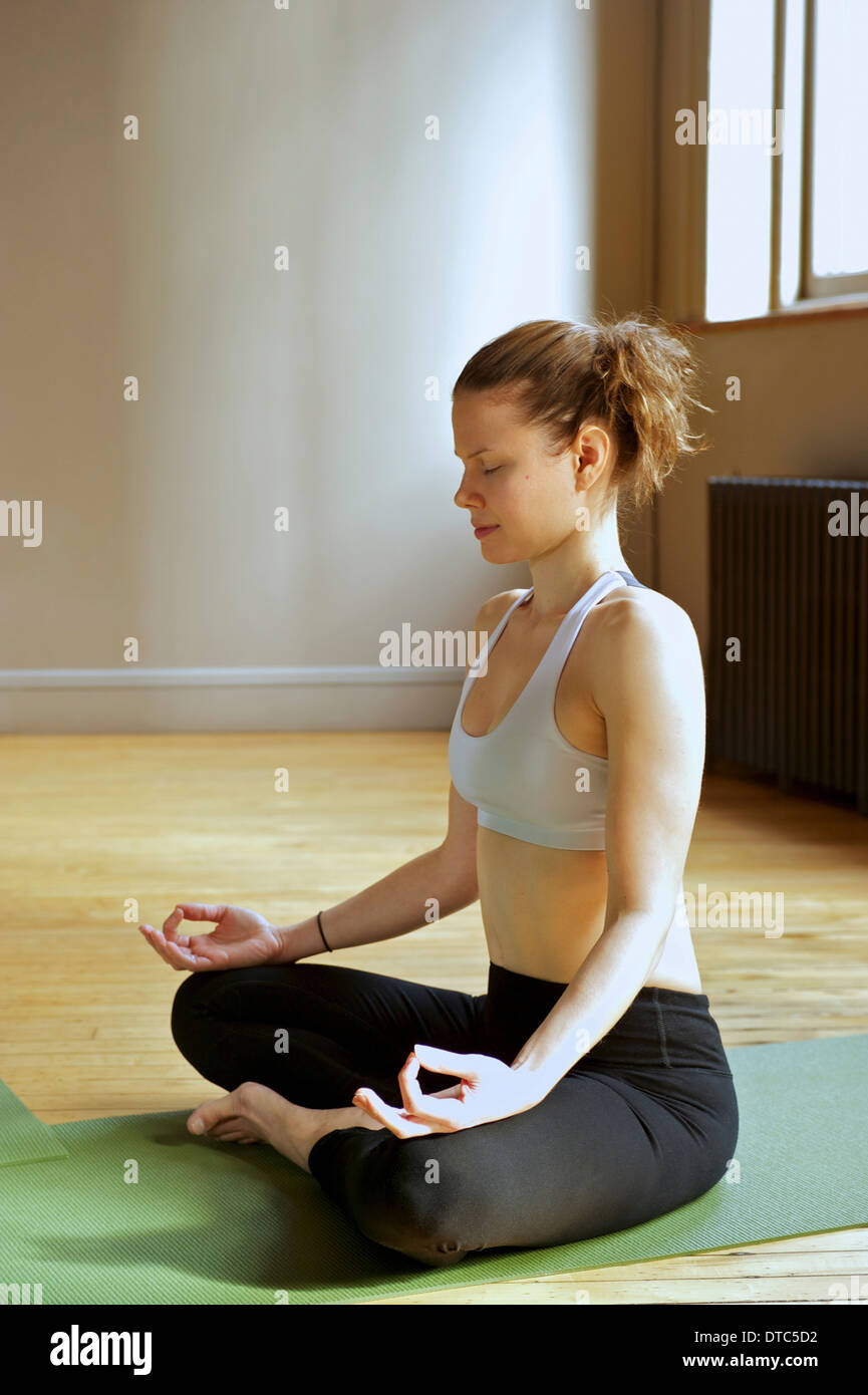 Mid adult woman in lotus pose - Stock Image