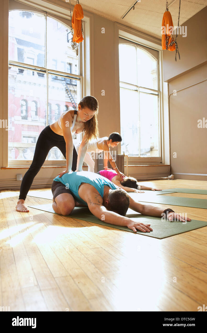 Yoga teachers assisting people in class - Stock Image