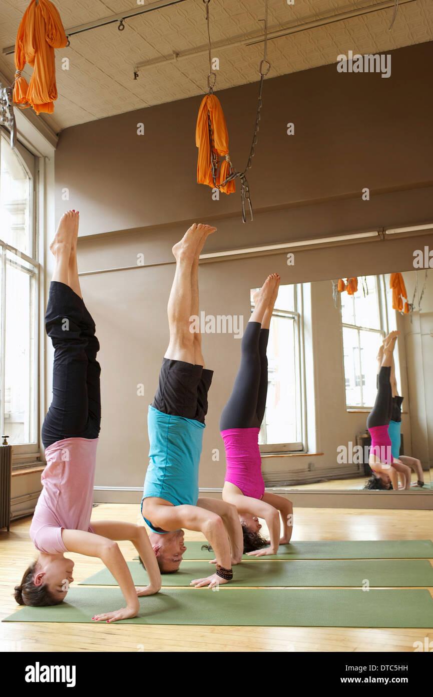 People doing headstands (Salamba-Shirshasana) in yoga class - Stock Image