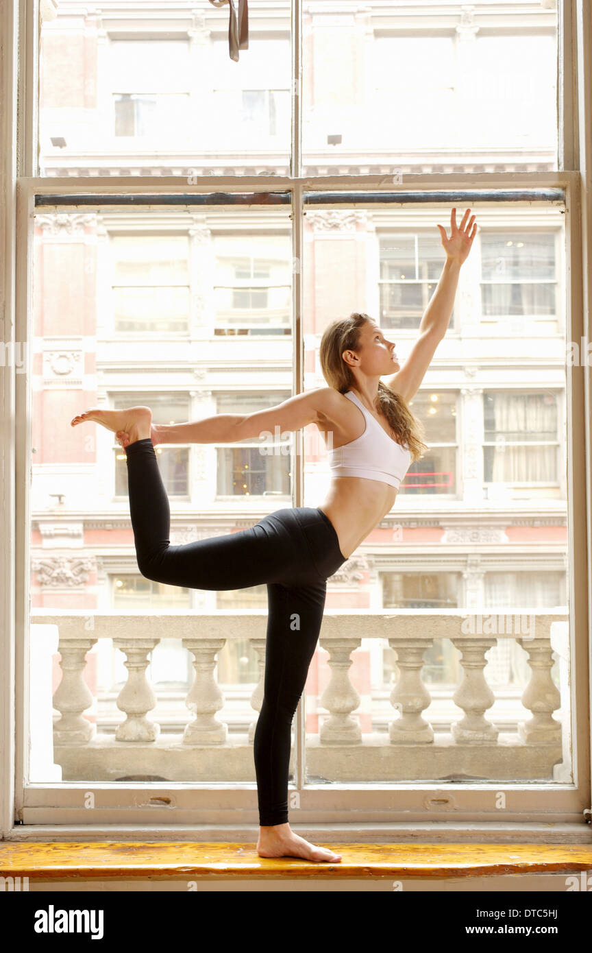 Woman doing dancer pose by window - Stock Image