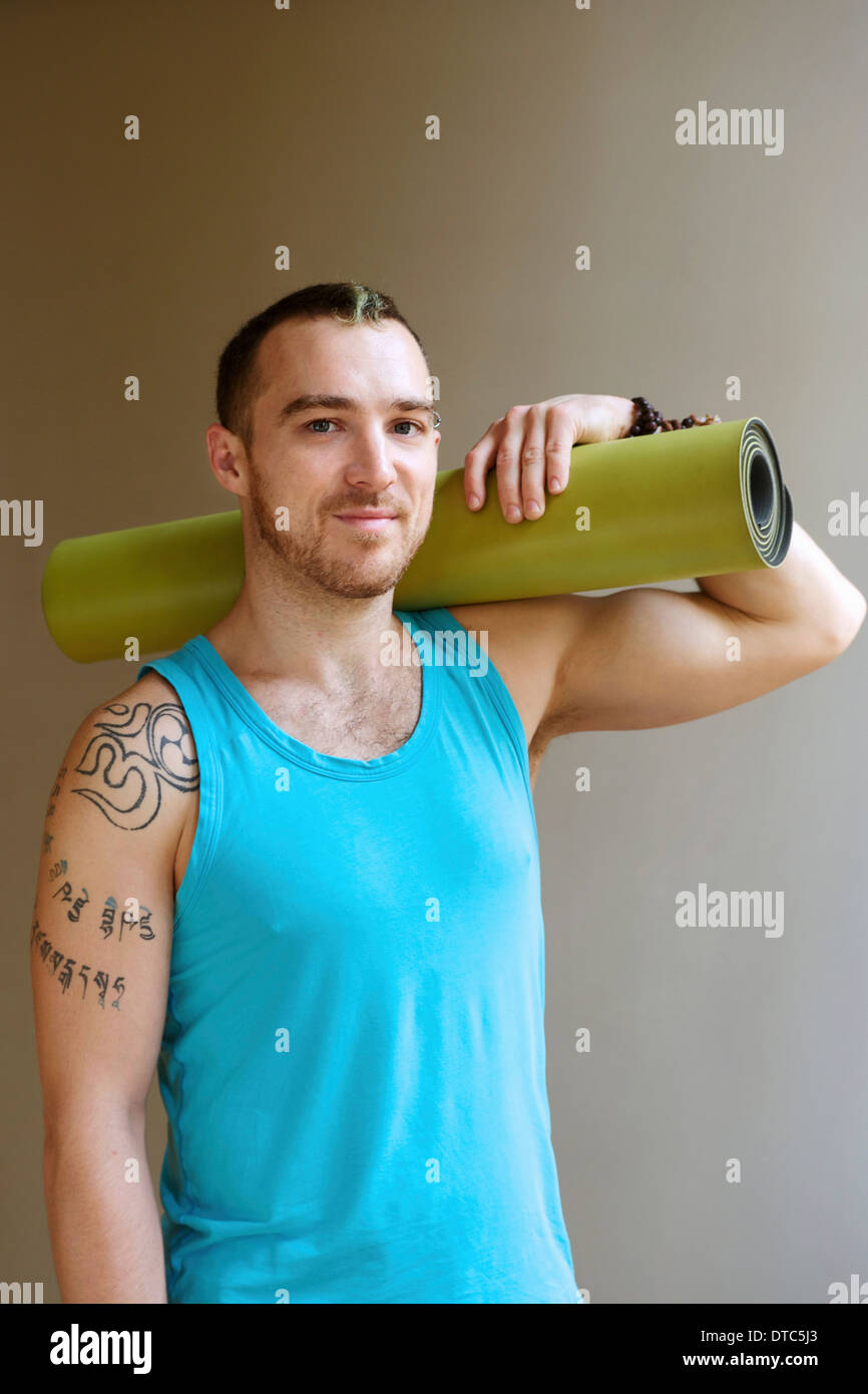 Portrait of man holding yoga mat - Stock Image