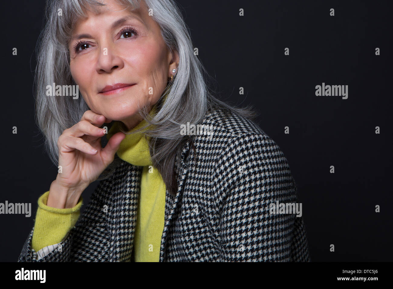 Studio portrait of attractive senior woman - Stock Image