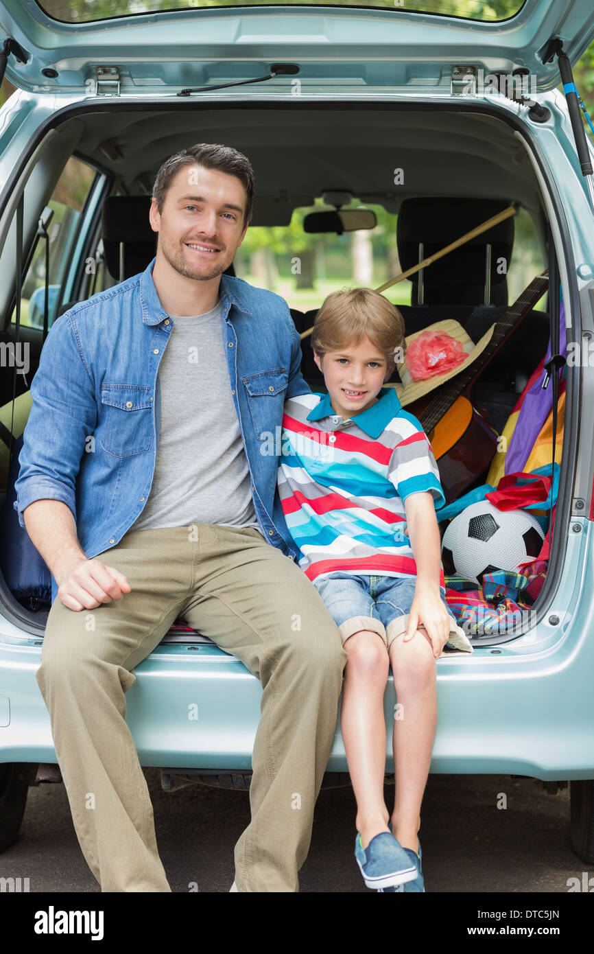 Portrait of father and son sitting in car trunk - Stock Image