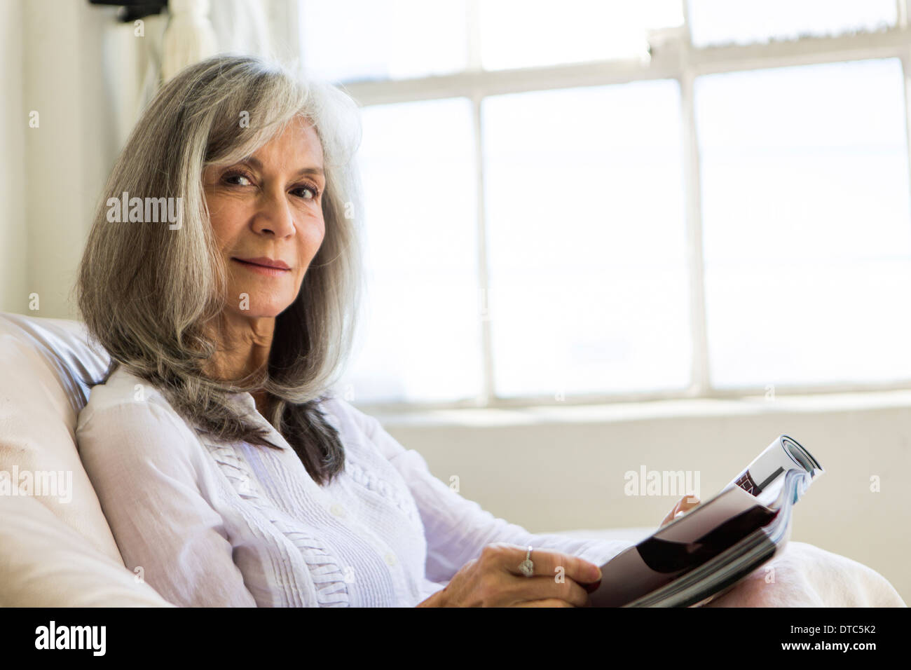Portrait of attractive senior woman reading magazine Stock Photo