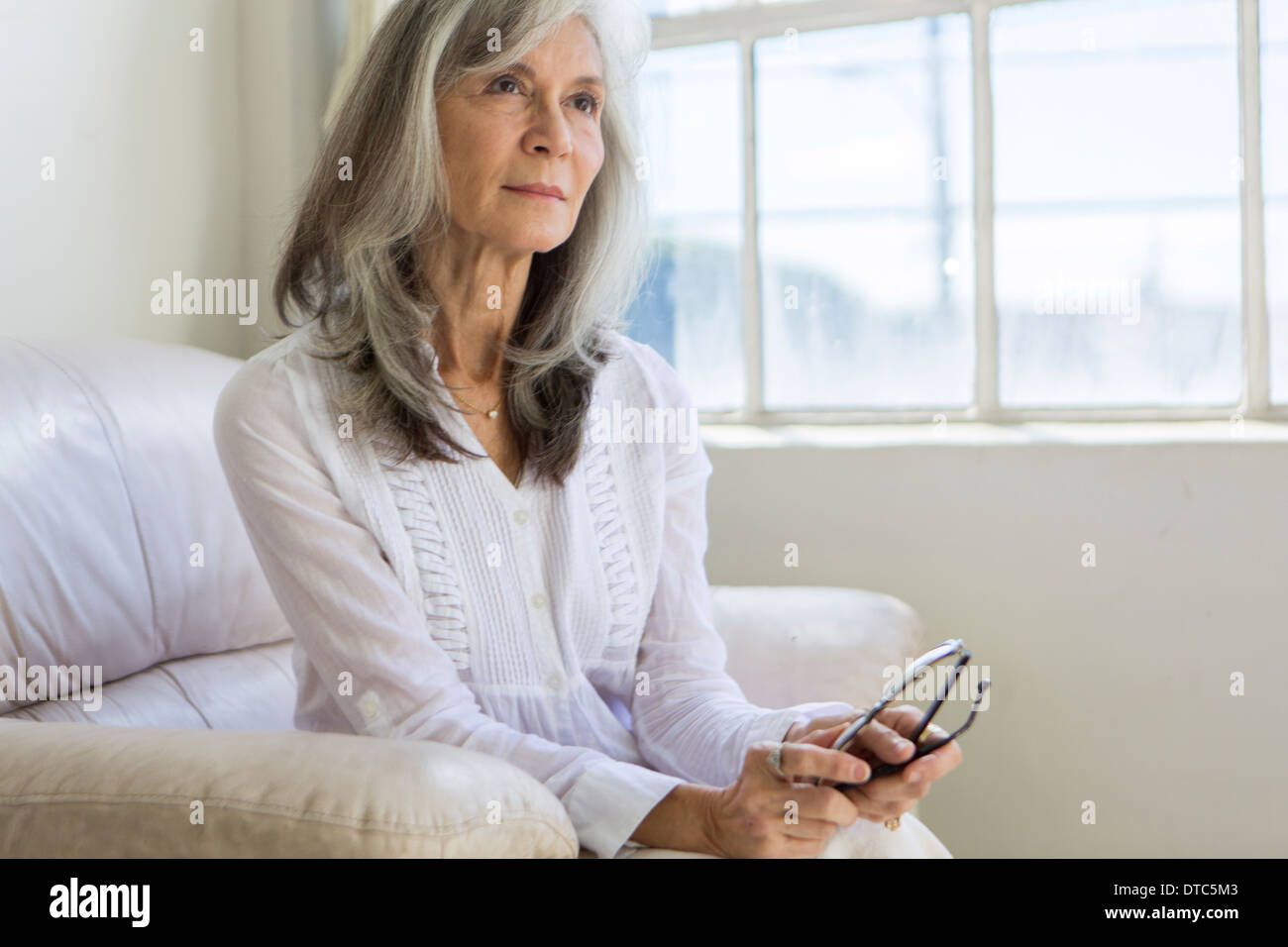 Portrait of attractive senior woman sitting in apartment - Stock Image