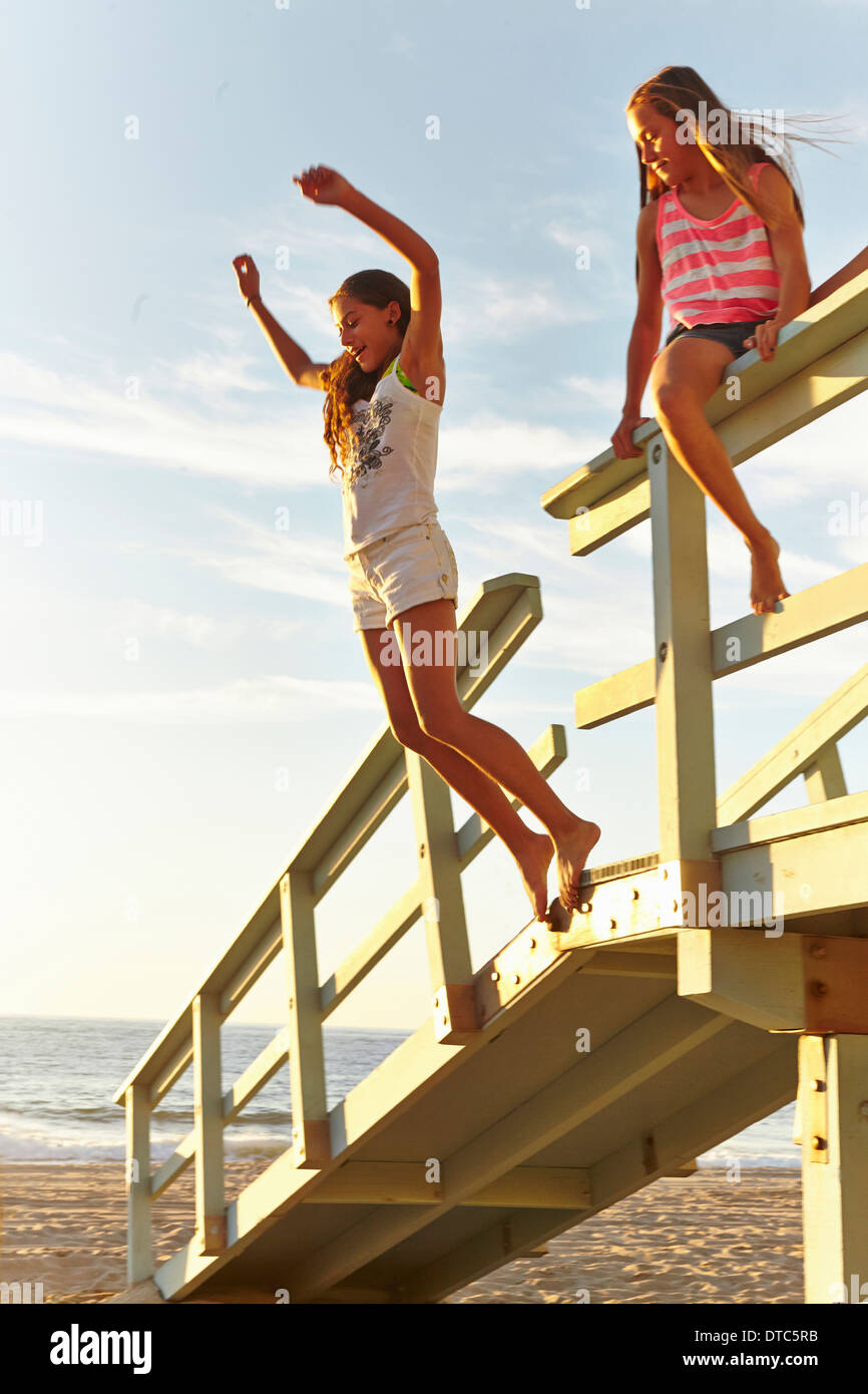 Two girls playing at beach, jumping off boardwalk - Stock Image