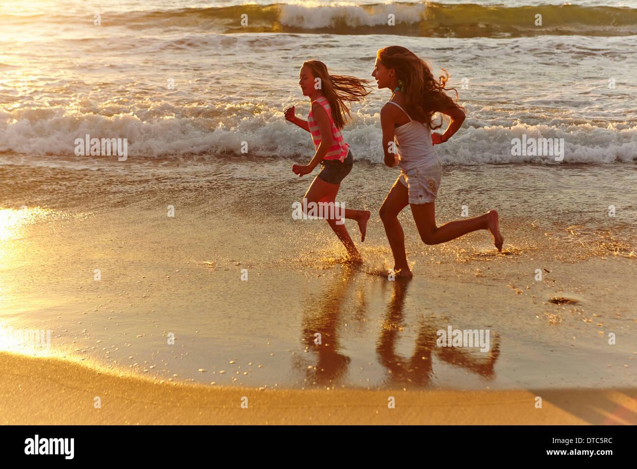 Two girls running along beach at sunset - Stock Image