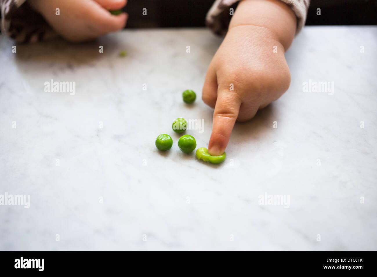Toddler girl squashing pea - Stock Image