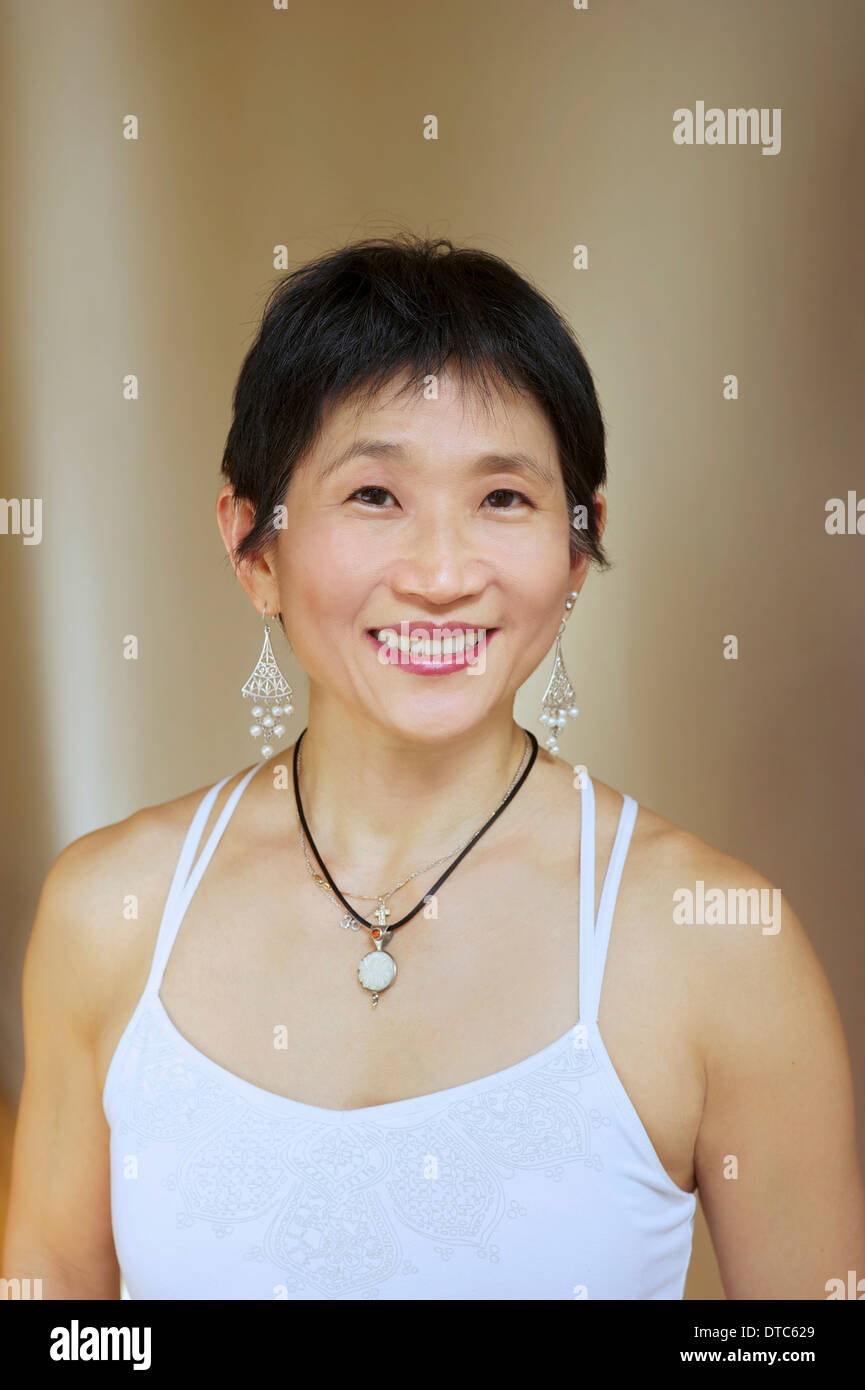 Portrait of mature woman in white vest Stock Photo