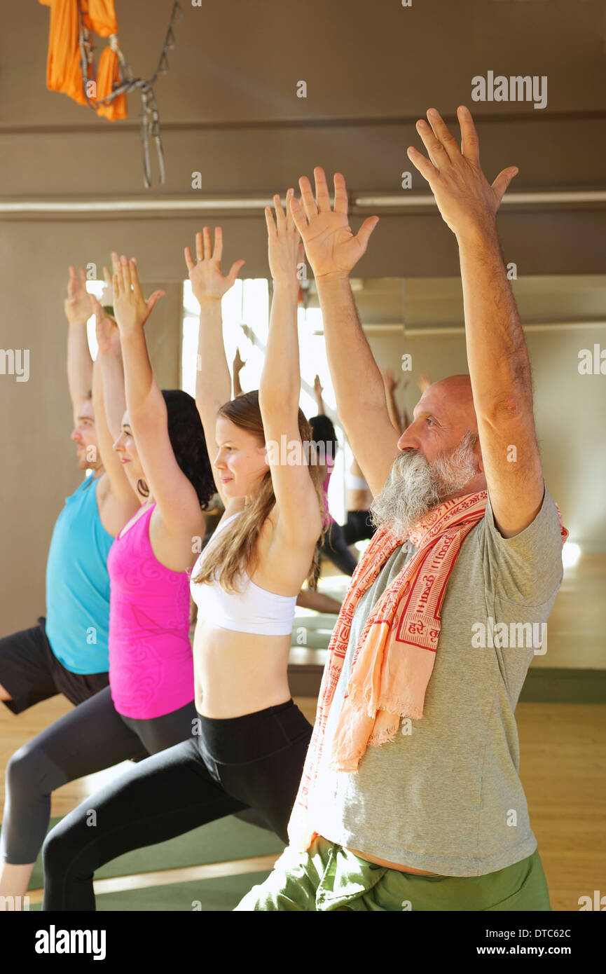 People in warrior pose in yoga class - Stock Image