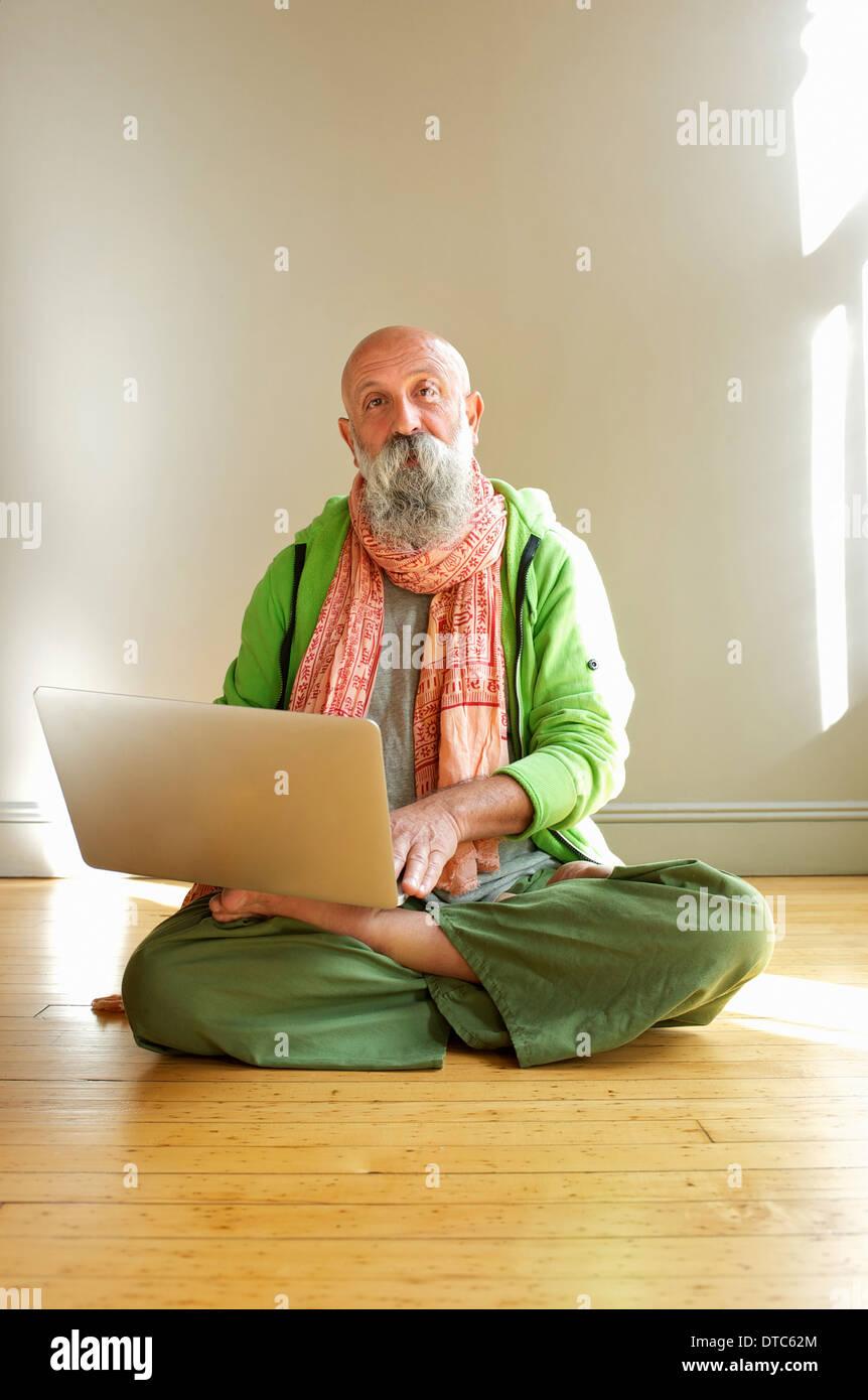 Senior man using laptop in lotus position - Stock Image