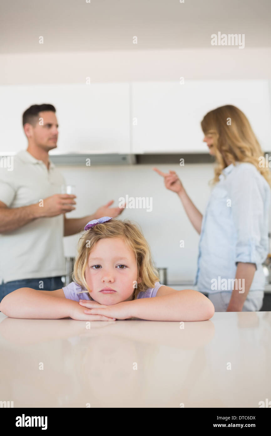 Sad girl leaning on table while parents conflicting - Stock Image